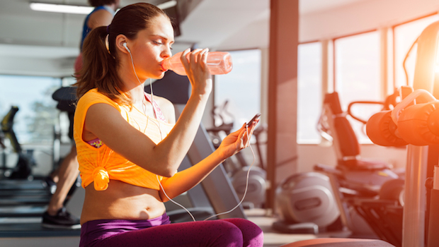 Woman in gym drinking water - HOW LONG SHOULD MY WORKOUT BE blog post