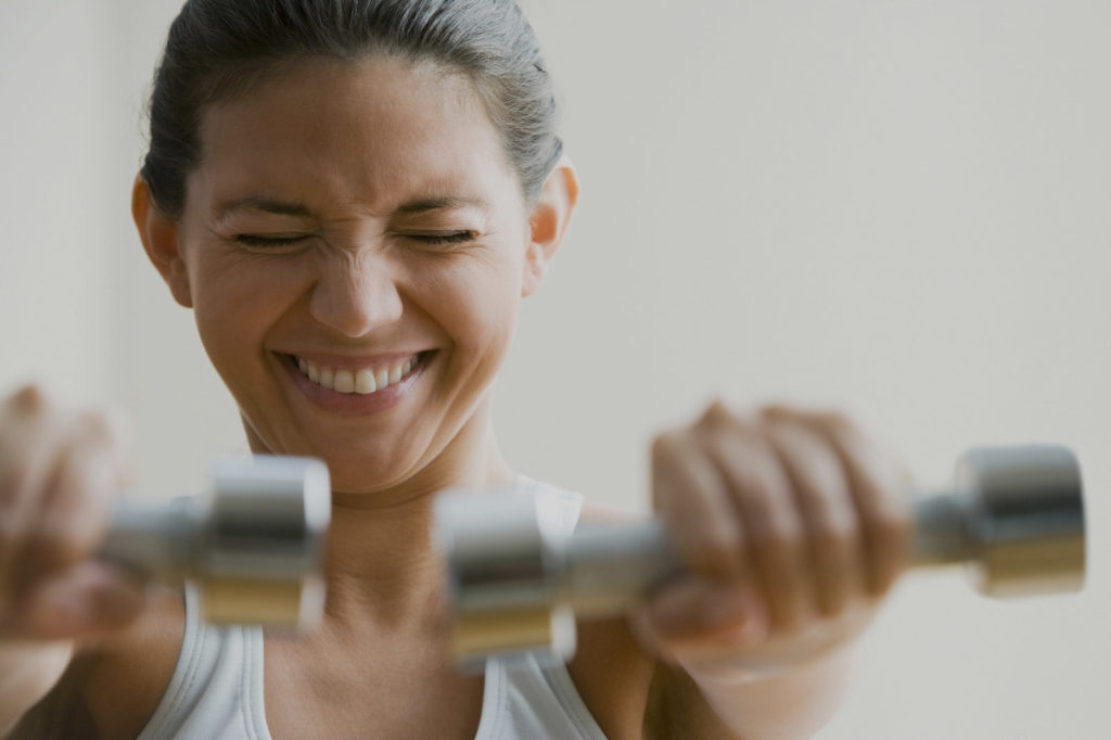 Woman with arms extended with free weights