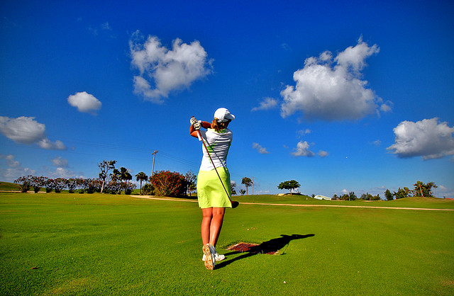 Woman golfing outside - The Golf Swing blog post