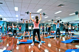 People in gym raising exercise bar above head - Time to exercise blog post