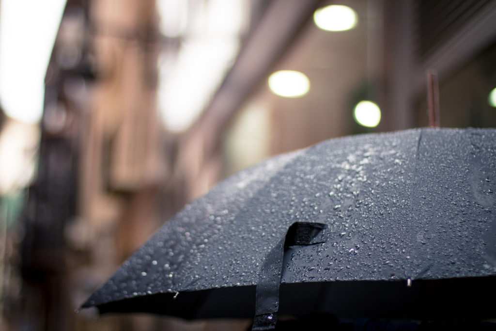 Open black umbrella outside while raining - Arthritis – is it your personal barometer blog post