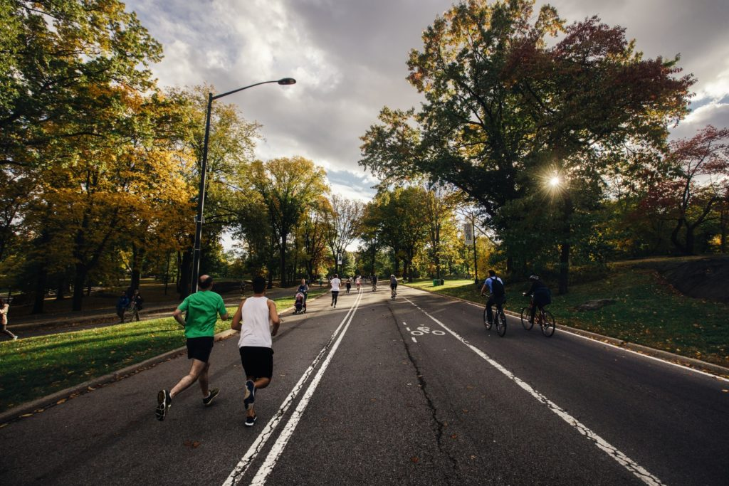 People jogging and biking outside on street - Enjoy Exercise Outdoors blog post