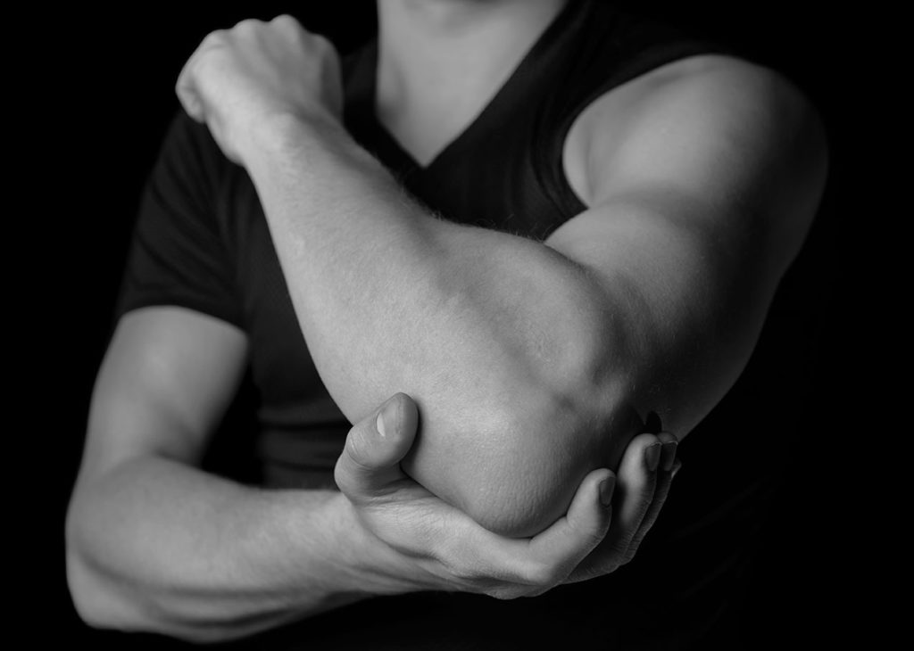 Grayscale image of man holding his elbow - What can I do to reduce post workout muscle soreness from a nutritional point of view blog post