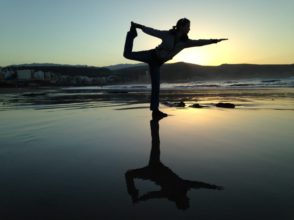 Woman in yoga position on beach - The all over sync…mind and body blog post