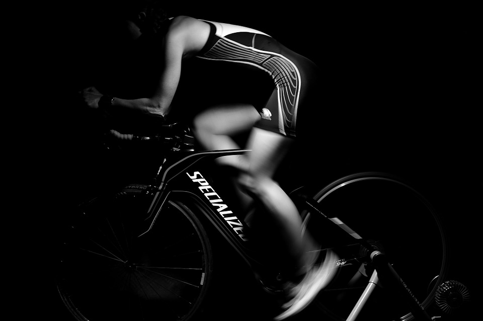 Grayscale image, person on stationary bike - A one hour workout is 4% of your day…so there should be no excuses blog post