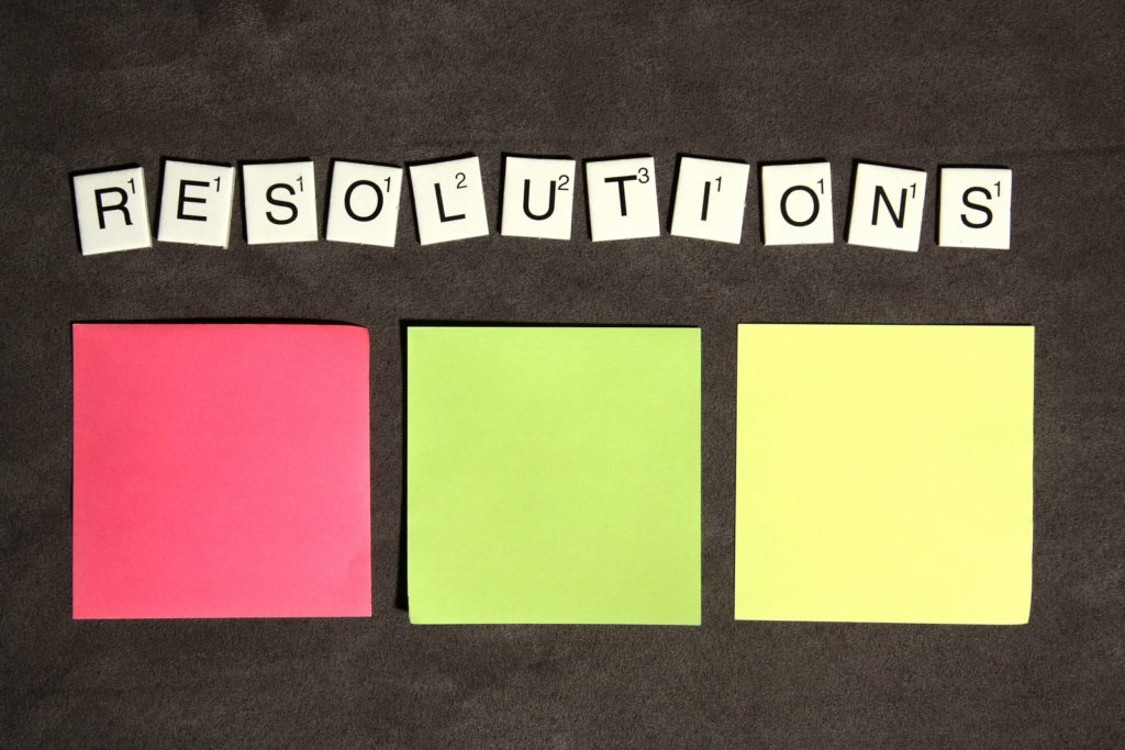 "Pink, green, yellow sticky pads with letter tiles spelling ""resolutions"" - Want some help with your New Year's Resolutions blog post"
