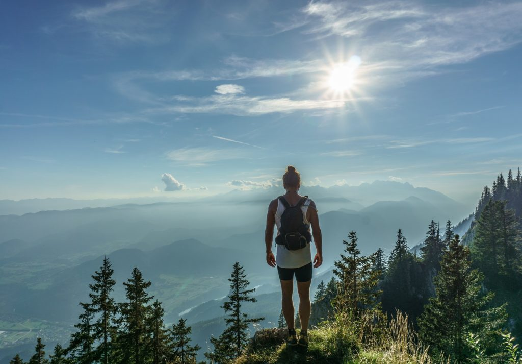 Woman with backpack on mountain - 7 ways to live a healthier lifestyle blog post