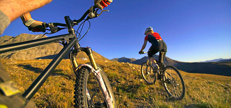 Two bikers riding off road in the hills - Returning to Exercise after Injury blog post