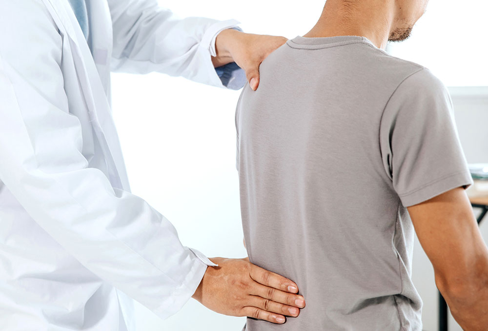 Doctor with young man experiencing back pain