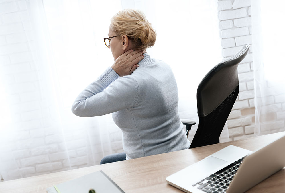 Older woman with computer on desk with neck pain