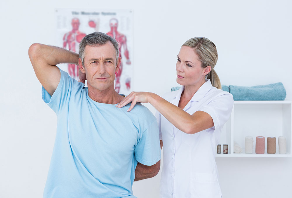 Physiotherapist with older man experiencing back pain