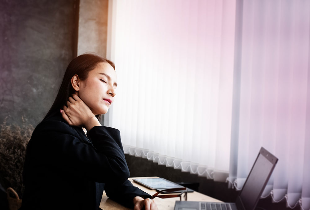 Young woman sitting in front of computer with neck pain